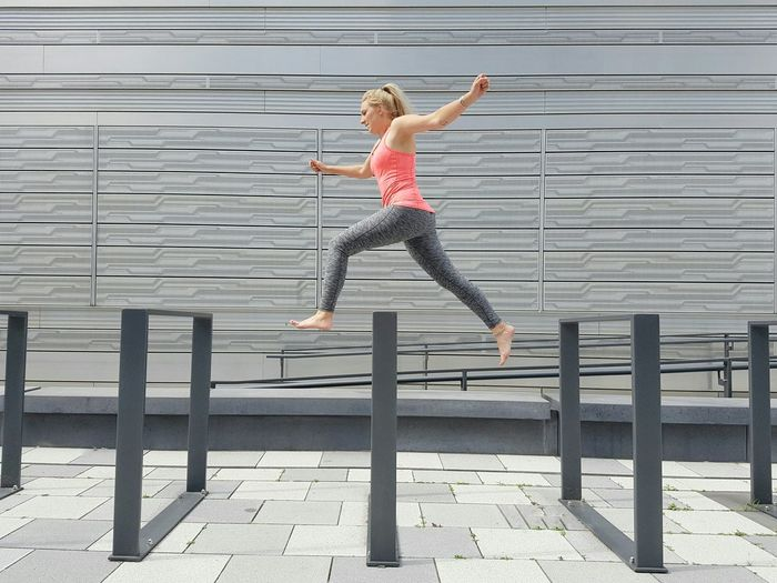 Jump Modern Architecture Facades Wall Silver  Shades Of Grey Woman Jumping Running Building Exterior Young Adult Pedestrian Walkway Outdoors Doing Sport The Color Of Sport Hurdles Race Athletic Healthy Lifestyle Sportswear Pink Top Embrace Urban Life Streetphotography Urban Geometry Stories From The City