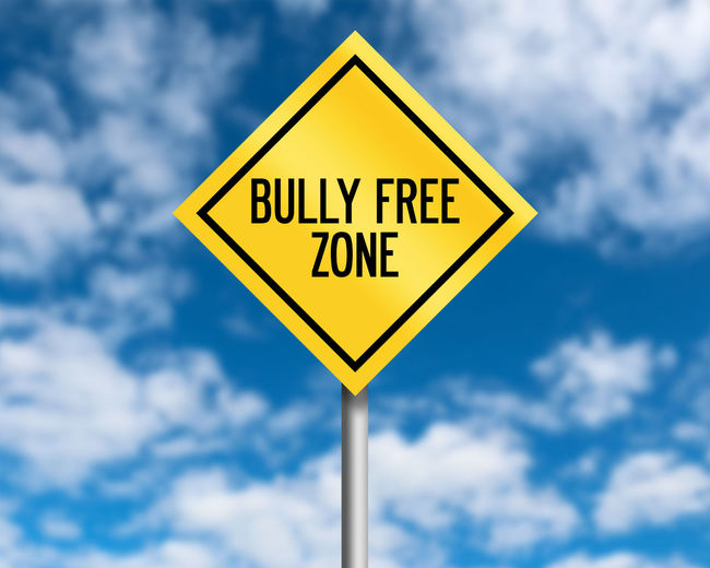 Bully Free Zone Blue Bully Bullying Classroom Cloud - Sky Communication Day Diamond Shaped Focus On Foreground Geometric Shape Information Low Angle View Nature No People Outdoors Road Road Sign Shape Sign Sky Text Warning Sign Warning Symbol Yellow