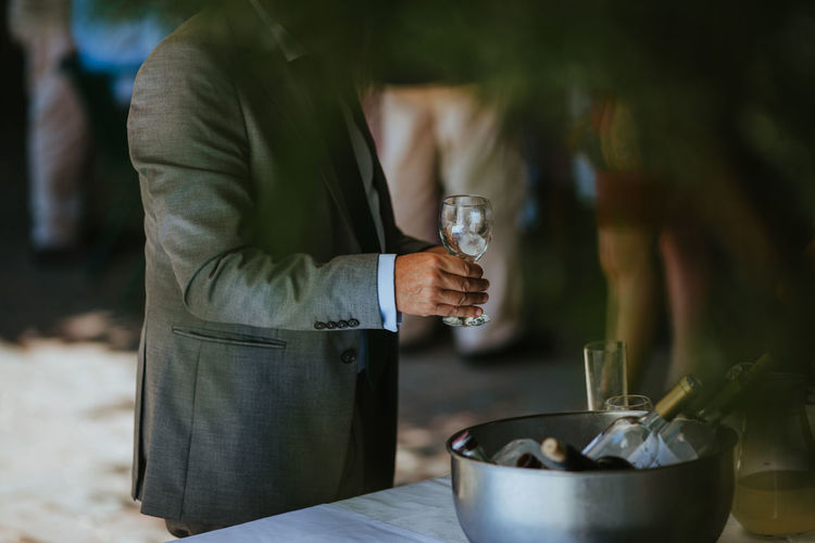 Midsection of man holding wineglass while standing at table indoors