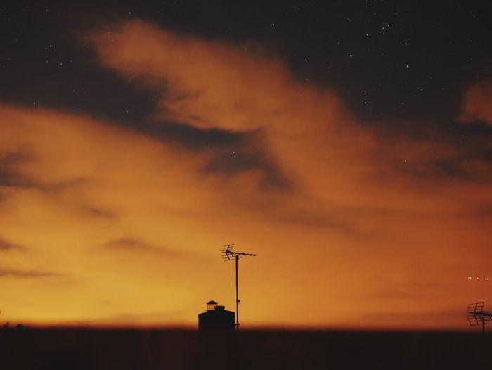 Silhouette antenna against orange sky