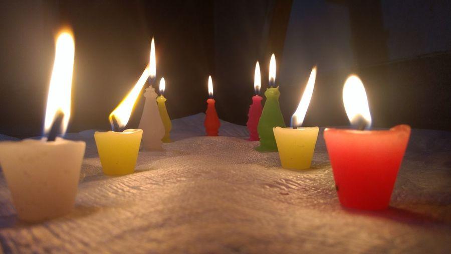 Lit candles burning in darkroom