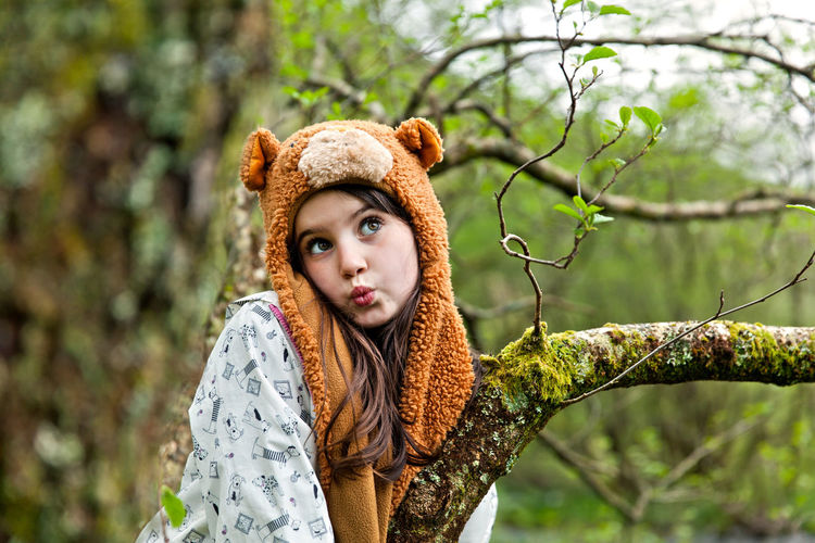 Girl Wearing Knit Hat Puckering Lips By Tree In Forest