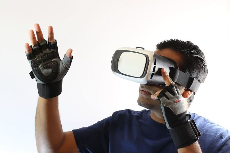 Man wearing virtual reality goggles and gloves pressing button on headset 3D American Cyberspace Display Eyeglasses  Future Futuristic Game Gamer Gloves Goggles Headset Indian One Person Playing Reaching Out Spanish Technology Technology Everywhere Virtual Reality Virtual Reality Simulator Vision Waving Wearable Computer White Background