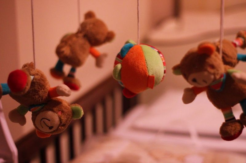 Stuffed toys hanging over crib at home