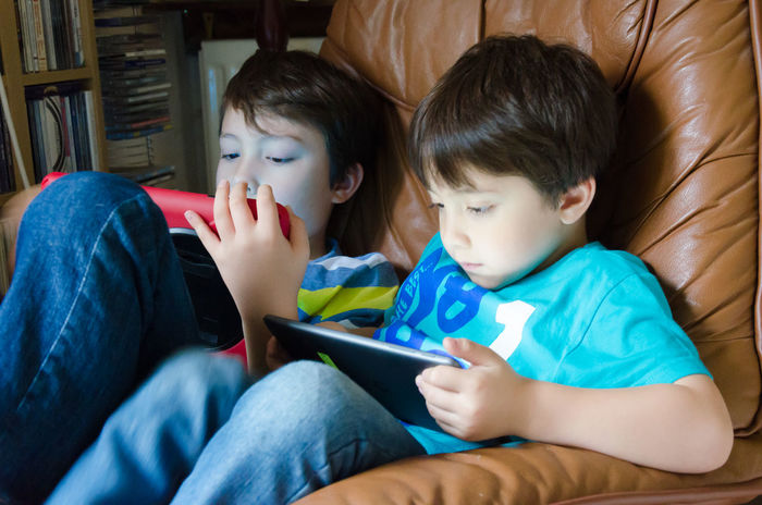 Brothers sit together in a dark room playing on their tablets. Children Sitting Boys Brothers Childhood Closeness Day Digital Tablet Indoors  People Playing Real People Seated Sitting Tablets Technology Togetherness Togetherness Friendship Touch Screen Two People Wireless Technology