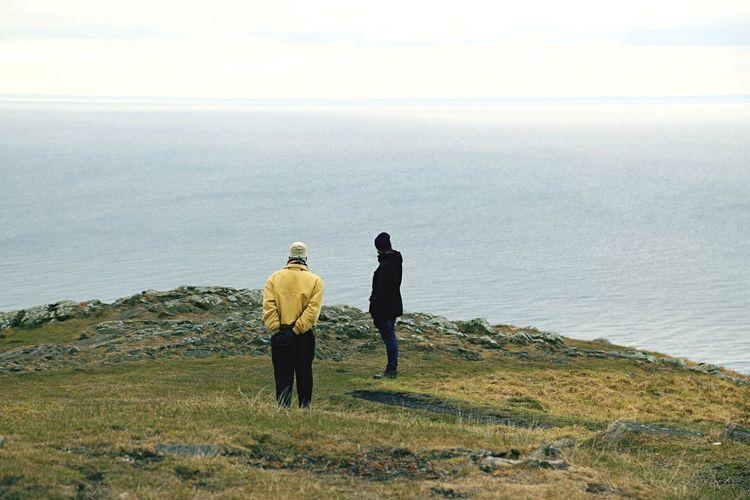 Men standing on hill against sea