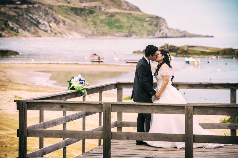 Couple Kissing While Standing On Pier By Sea Against Sky