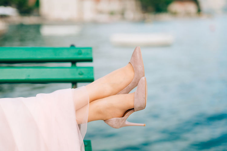 Cropped image of hand on bench against sea