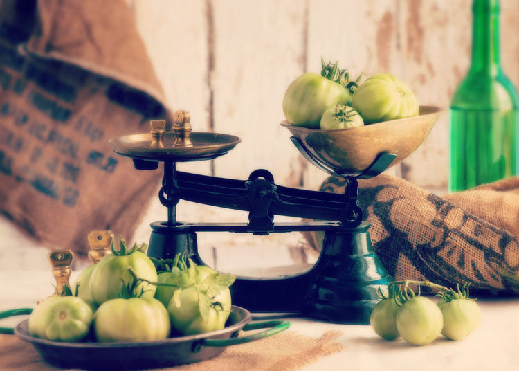 Green tomatoes in weight scale on table
