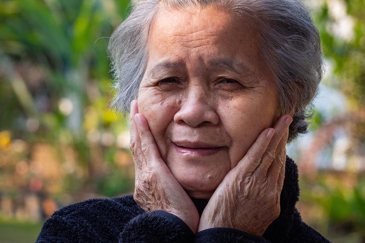 Portrait of a happy elderly woman smiling in garden.