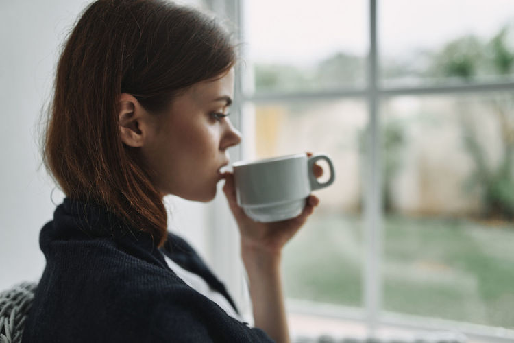 Young woman drinking coffee by window