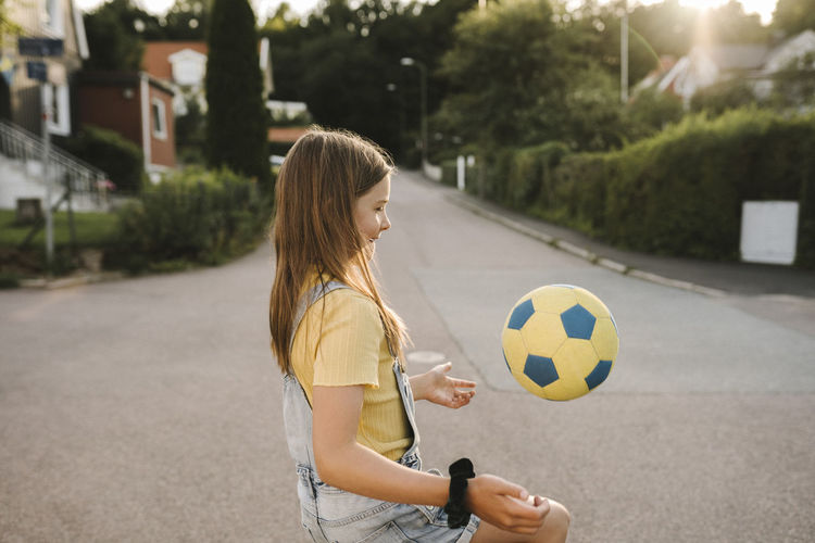 Woman playing soccer ball in city