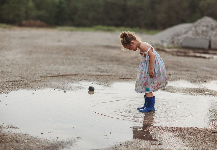 Full Length One Person Childhood Child Real People Girls Casual Clothing Land Water Standing Innocence Outdoors Rain Side View Rainy Season Boots Dramatic Sky Puddle Spring Ripples