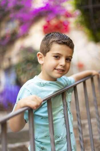 Portrait of boy standing by railing