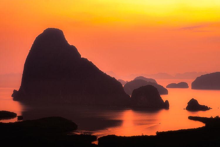 Silhouette rocks in sea against orange sky
