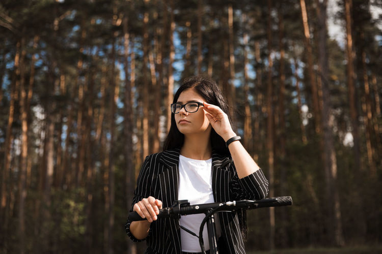 Low angle view of woman wearing eyeglasses standing against trees