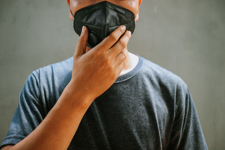 Midsection of man wearing pollution mask
