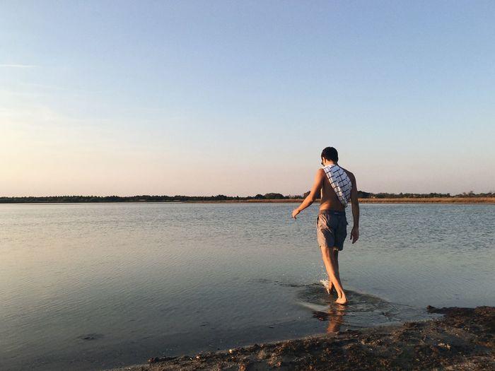 Rear View Of Shirtless Man Walking At Lakeshore During Sunset