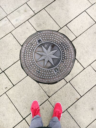 Low Section Of Man Standing By Manhole On Footpath