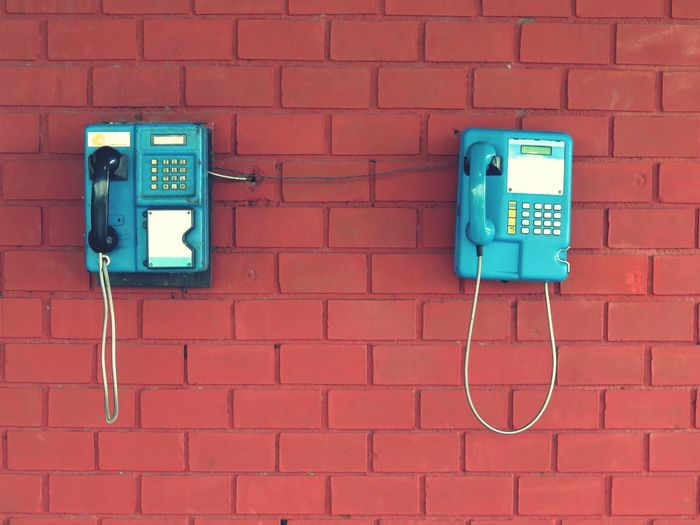 Blue pay phones on brick wall