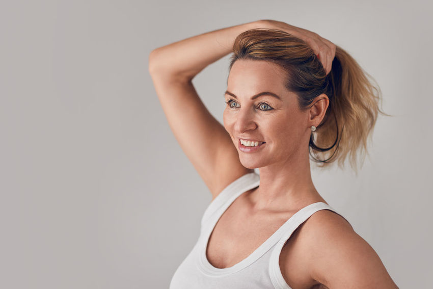 Attractive blond woman holding up her long hair Beautiful Copy Space Hair Happiness Happy Woman Attractive Beauty Best Ager Blond Face Gray Background Holding Hair Up Indoors  Middle-aged One Person One Woman Only Portrait Smiling Studio Shot