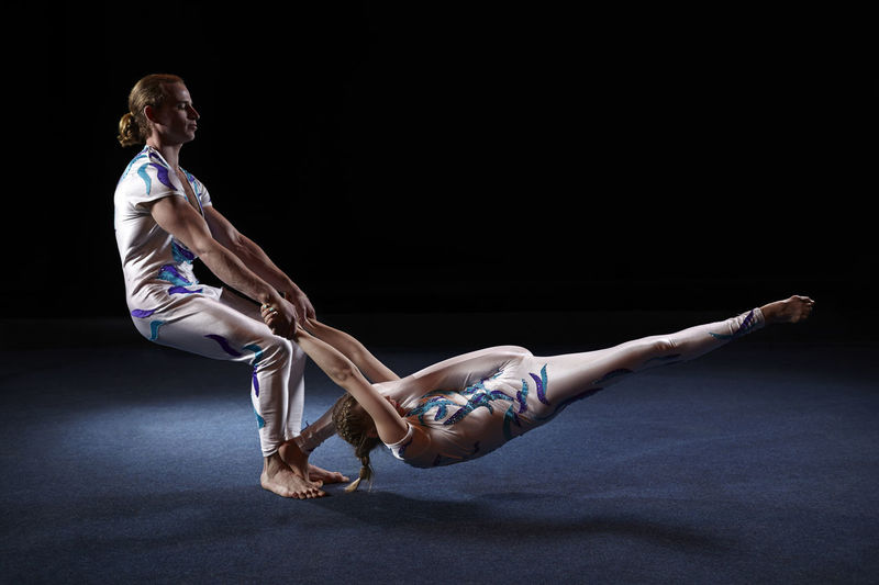 Man and woman performing acrobatics on black background