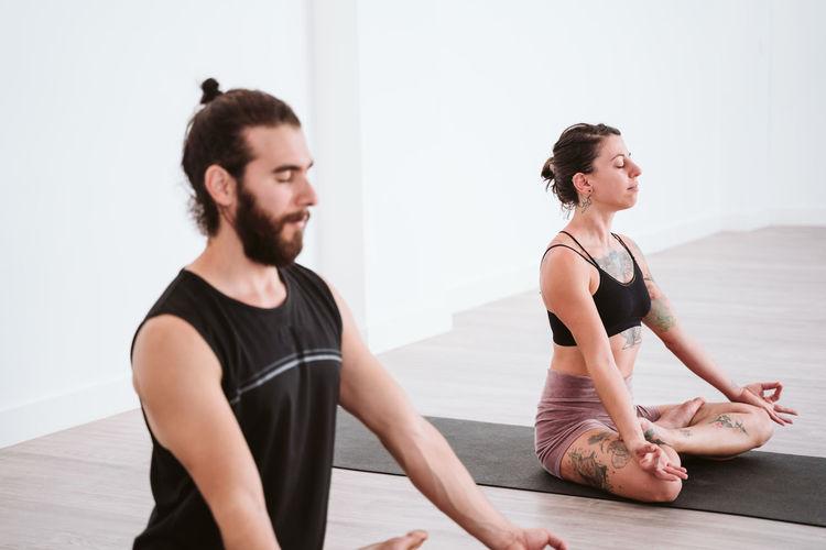 Man and woman doing yoga on floor
