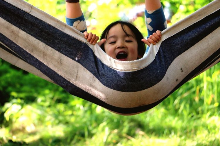 Low angle view of boy playing on slide at park