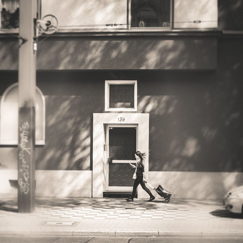 Rear view of man sitting on footpath against building
