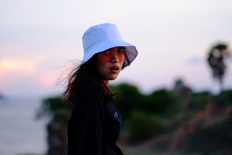 Portrait of young woman in hat and sunglasses standing against sky during sunset
