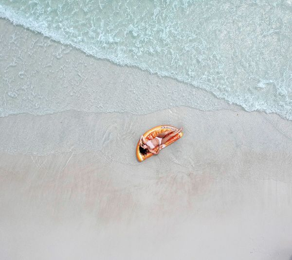 High angle view of woman lying at beach