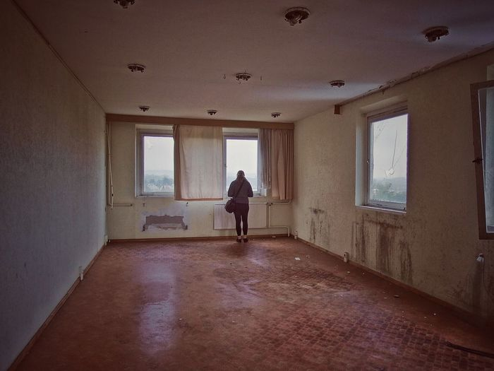 Full length rear view of woman standing in abandoned room