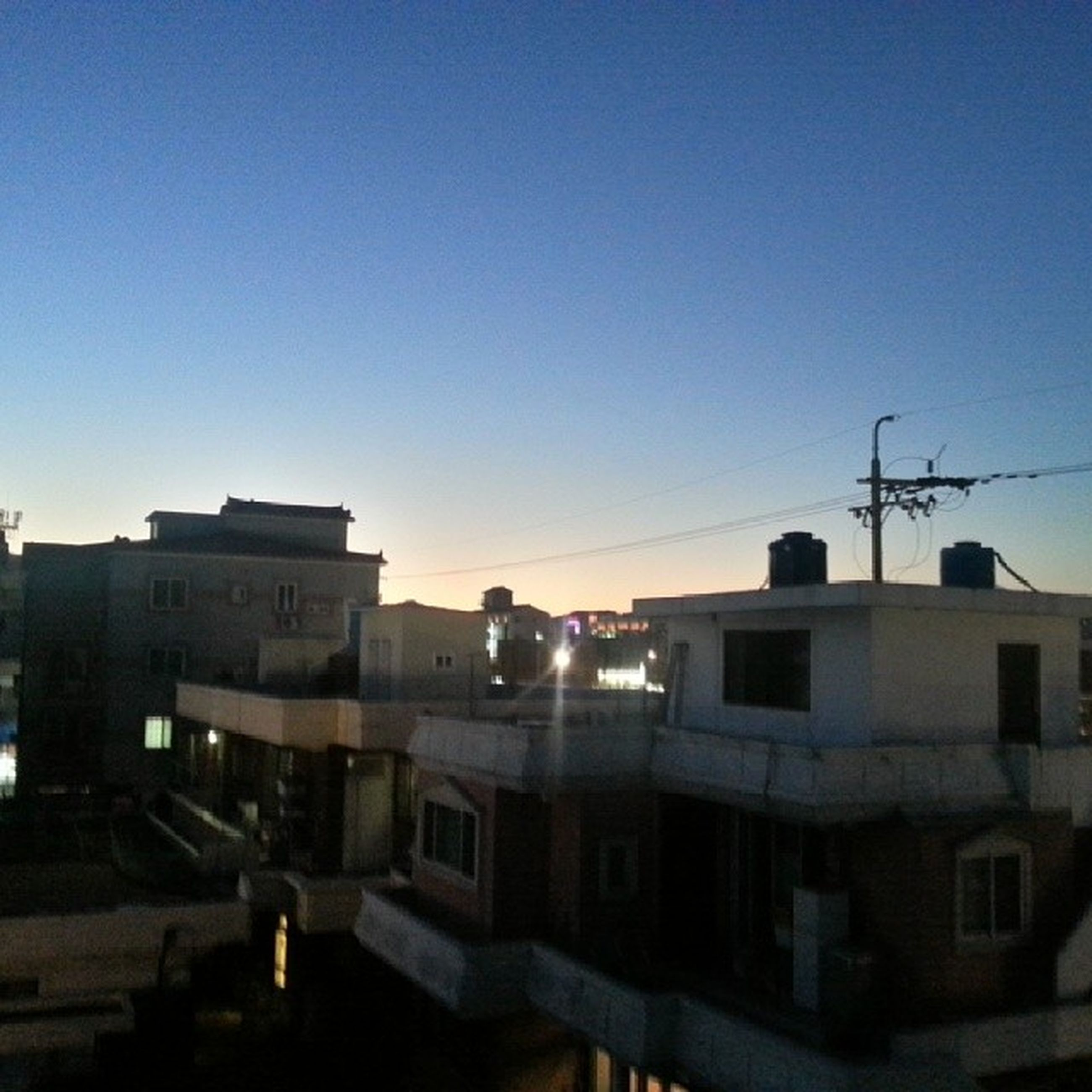 building exterior, clear sky, architecture, built structure, copy space, blue, city, street light, residential structure, residential building, building, house, sunlight, power line, street, outdoors, dusk, sky, no people, illuminated