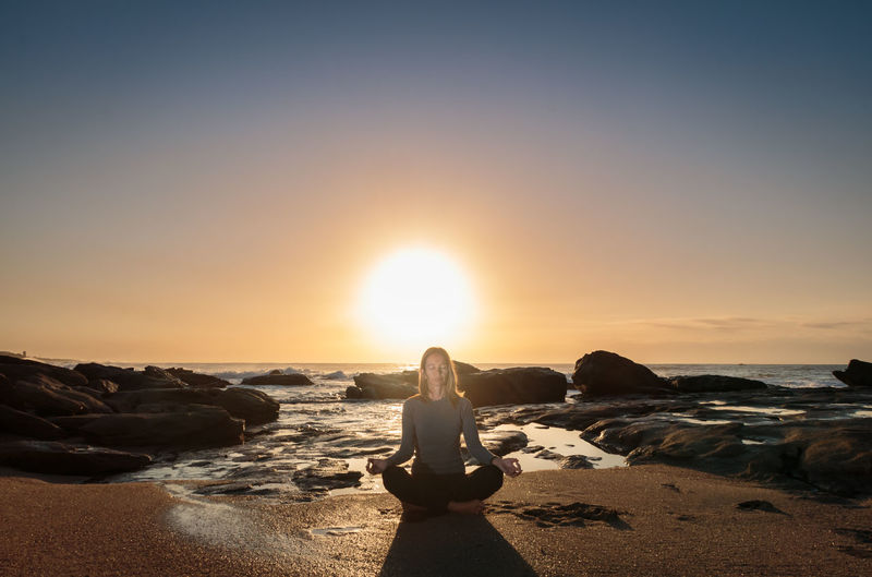 Young Woman Meditating On Shore At Beach During Sunset