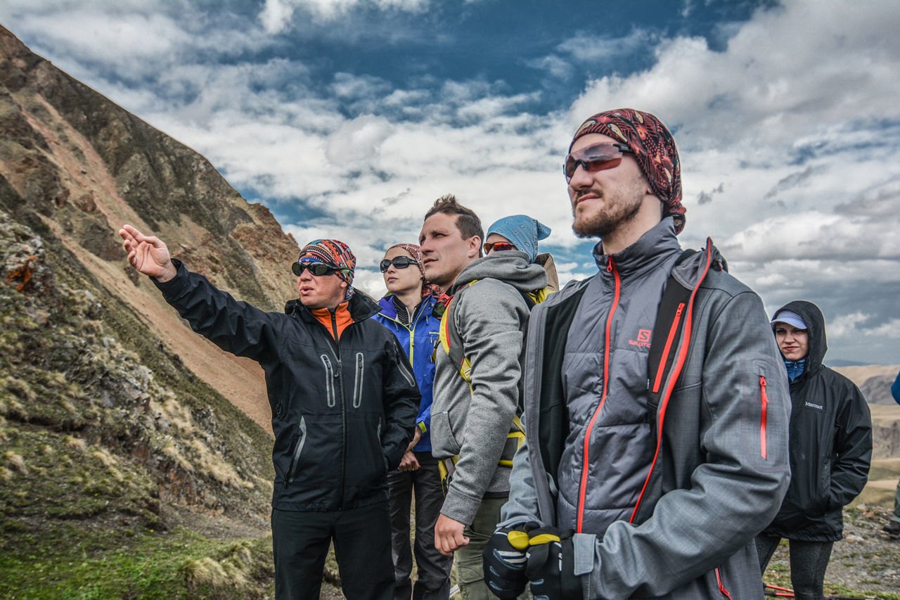 sky, mountain, young men, cloud - sky, young adult, togetherness, leisure activity, real people, day, adventure, outdoors, friendship, young women, lifestyles, low angle view, men, nature, smiling, hiking, sport, bonding, happiness, beauty in nature, warm clothing, people, adult, adults only