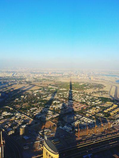 Shadow Of Burj Khalifa On Buildings In City Against Clear Blue Sky During Sunny Day