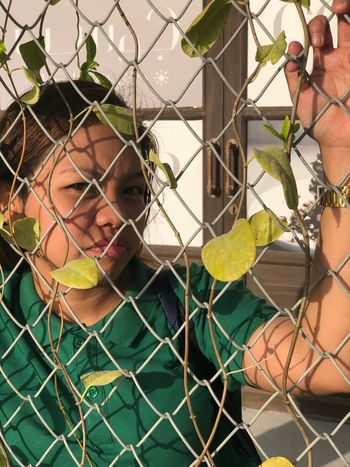 Fence One Person Chainlink Fence Portrait Real People Barrier The Portraitist - 2018 EyeEm Awards Plant Day Front View Outdoors Women Young Adult