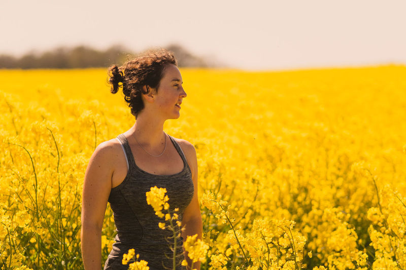 Young woman amidst yellow flowers in field