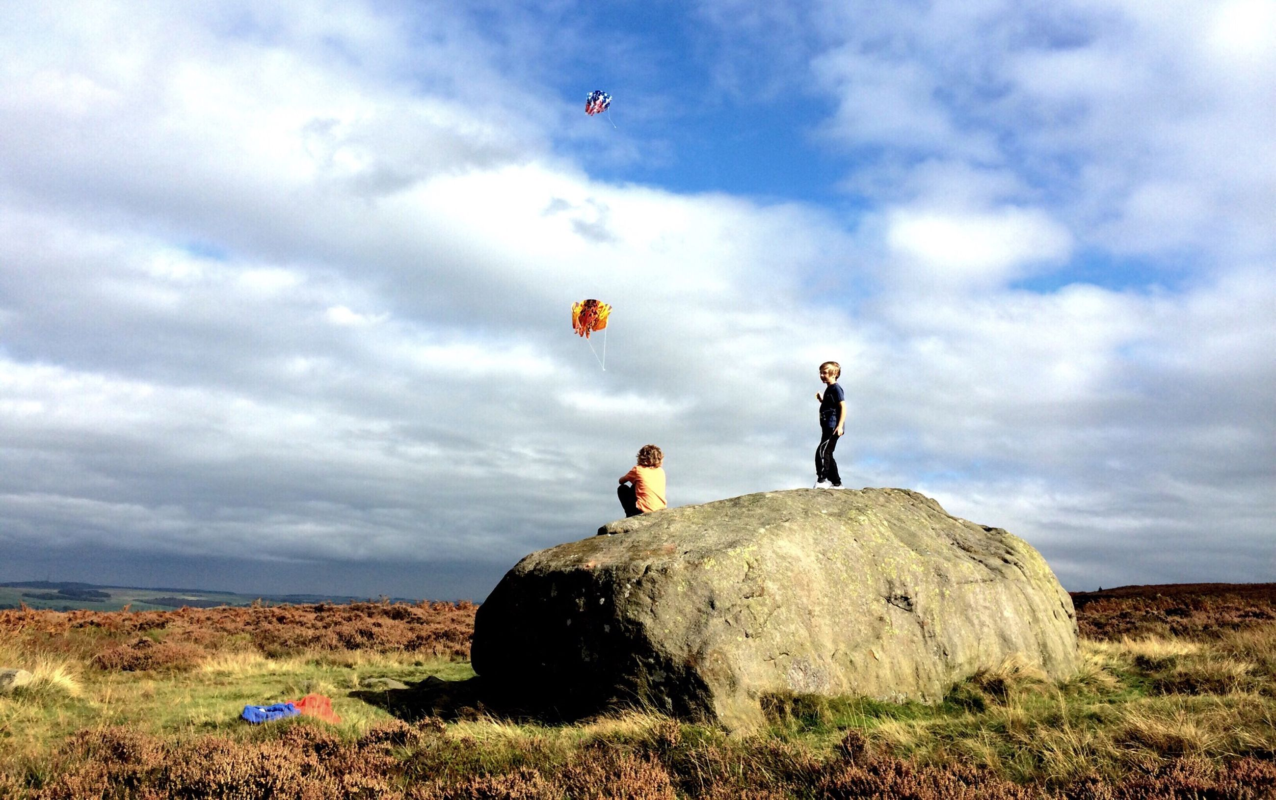 sky, lifestyles, leisure activity, cloud - sky, full length, men, cloudy, casual clothing, childhood, landscape, standing, cloud, boys, rock - object, nature, scenics, tranquility