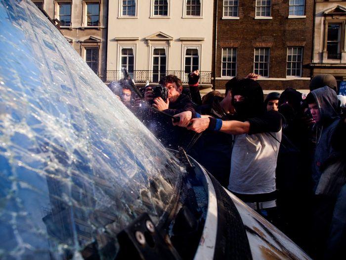 Protestors breaking windshield of vehicle against building