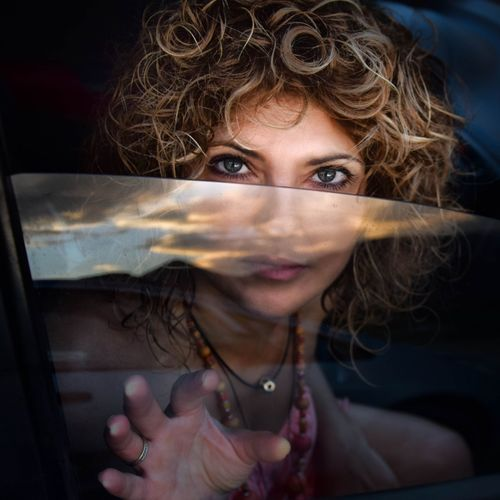 Portrait of woman with curly hair sitting in car