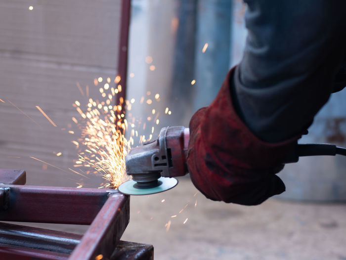 Worker grinding metal and welding metal with many fire sparks Metal Industry Human Hand Manufacturing Equipment Manual Worker Working Occupation Industry Workshop Factory Welder