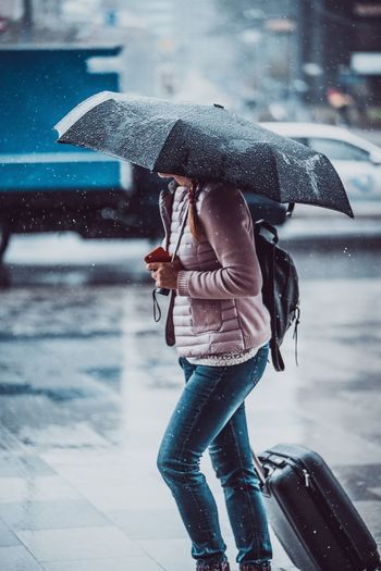 Woman Carrying Umbrella While Walking With Wheeled Luggage During Rainy Season