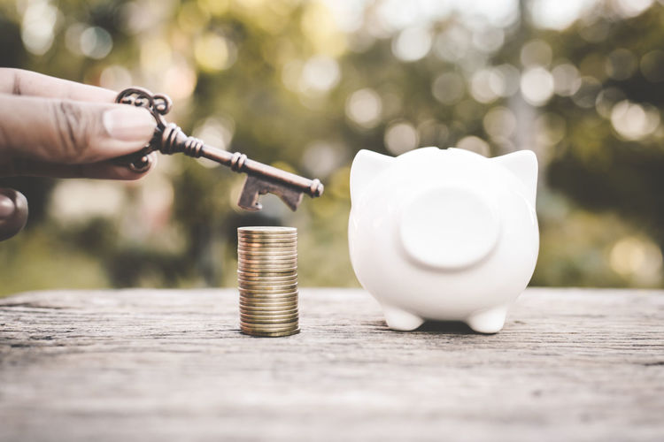 Cropped Hand Holding Key Over Stack Of Coins And Piggy Bank At Table