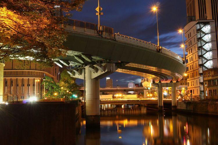 Illuminated modern bridge against sky at night