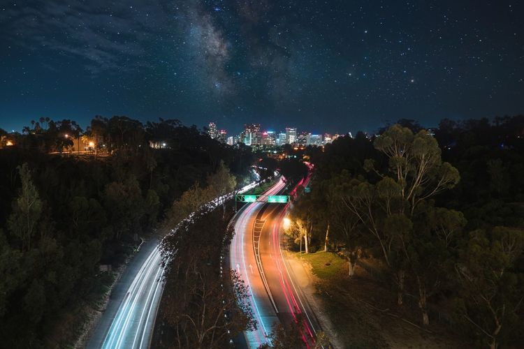 Panoramic view of vehicles on road against sky at night