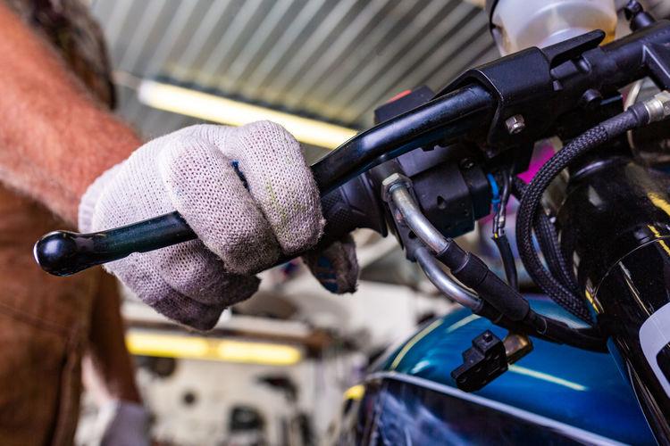 Midsection of mechanic repairing motorcycle in garage