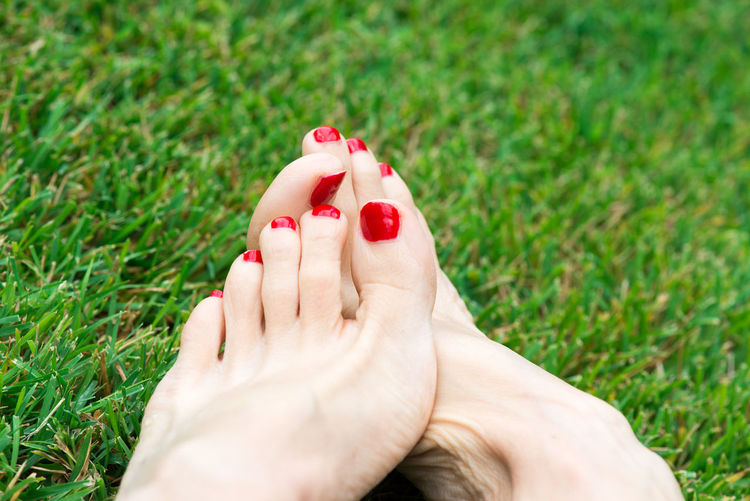 Low Section Of Woman With Painted Red Nail Polish On Field