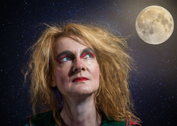 Close-up of woman with make-up against moon