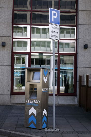 Architecture Building Exterior Built Structure City Communication Day Direction Electric Car Charging St Guidance Information Information Sign Nameplate No People Open Sign Outdoors Parking Sign Placard Road Sign Signboard Street Name Sign Text Western Script